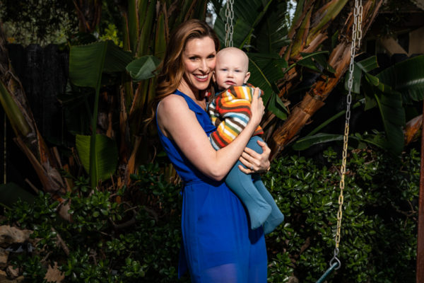 Emily Fletcher wears a blue short-sleeve dress and poses holding her infant child