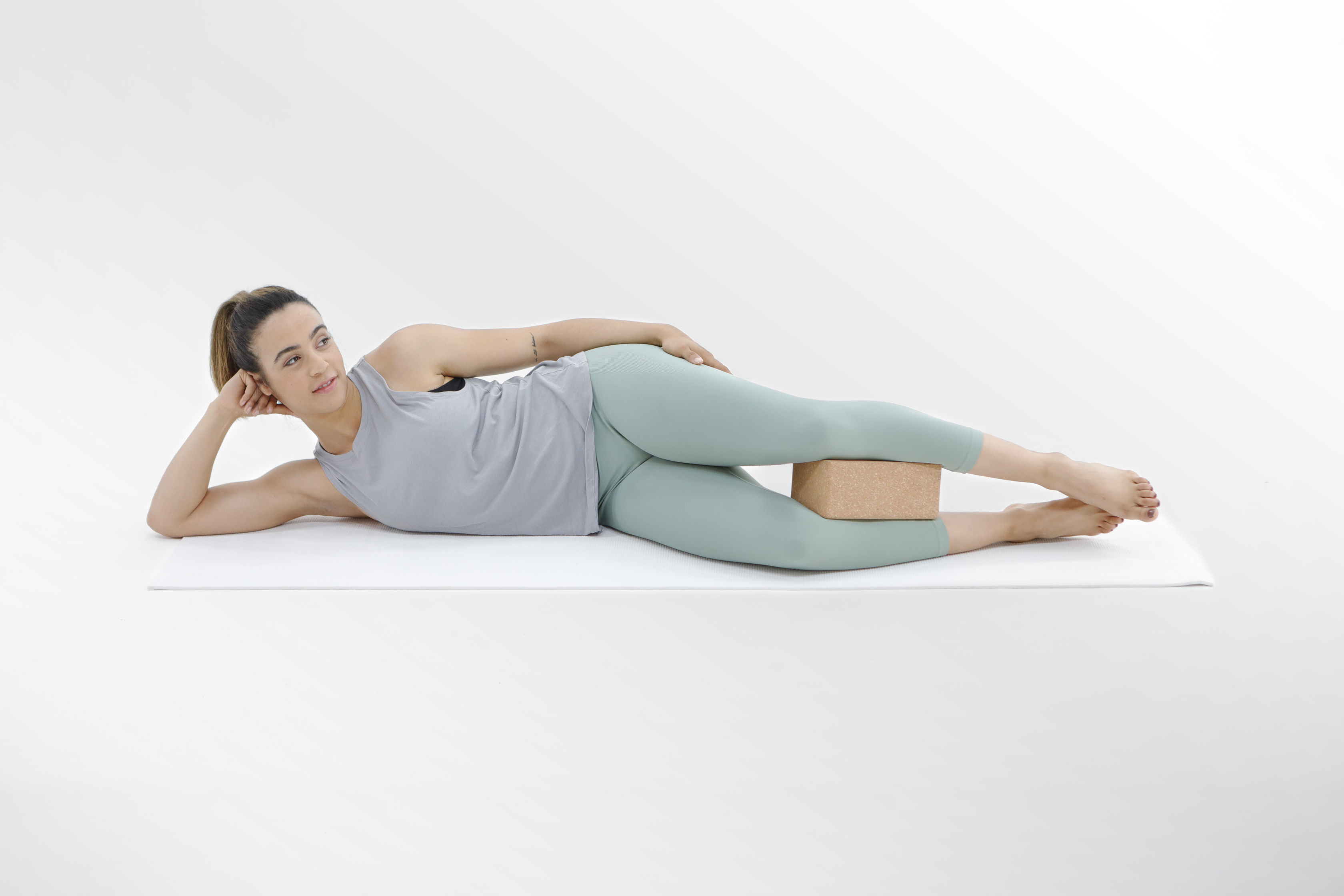 Model lying on her side with yoga block between legs