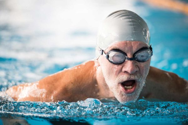 man swimming in pool with swimcap and goggles
